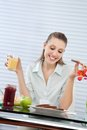 Happy woman having orange juice young looking down at plate of bread slices while Stock Photo