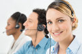 Happy woman with headsets smiling working other colleague in call center Stock Photo