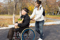Happy woman helping a disabled elderly man women men as she pushes his wheelchair along road on their return from doing the Royalty Free Stock Photography