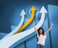 Happy woman with her arms raised up in front of arrows and statistic composite image on blue background Royalty Free Stock Photo