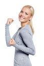 Happy woman with her fists up in gray sweater isolated on white Royalty Free Stock Images