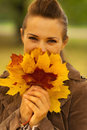 Happy woman hiding behind bunch of fallen leaves Royalty Free Stock Photos