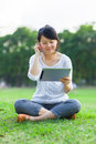 Happy woman holding at digital tablet and looking and sitting in park Stock Images