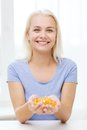 Happy woman holding fish oil capsules at home Royalty Free Stock Photo