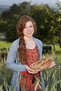 Happy woman holding a freshly baken bread breadin front of cornfield Royalty Free Stock Photos
