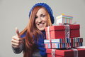 Happy woman holding piled christmas gifts a pile of and giving thumbs up in a positive mood Royalty Free Stock Image