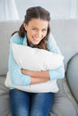 Happy woman holding pillow sitting on couch in bright living room Stock Images