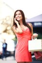 Happy woman holding shopping bags and using phone cell outdoors Royalty Free Stock Images