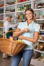 Happy woman holding shopping basket portrait of mid adult women with salesman in background Stock Photo