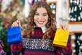 Happy woman holding small shopping bags in store portrait of young christmas Royalty Free Stock Photo