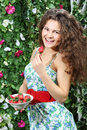 Happy woman holds plate with strawberries and brings one berry to mouth in garden Royalty Free Stock Image