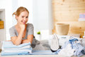 Happy woman housewife ironing clothes   in laundry at home Royalty Free Stock Photo