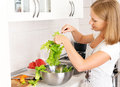 Happy woman housewife preparing salad in the kitchen vegetable Stock Image