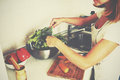 Happy woman housewife preparing salad in the kitchen vegetable Stock Photography