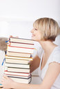 Happy woman with a huge stack of books side view hardcover piled high resting her chin on the top smile Stock Image