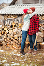 Happy woman hugging handsome man with axe in village Royalty Free Stock Photo