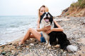 Happy woman hugging her dog on the beach Royalty Free Stock Photo