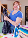 Happy woman irons a shirt Royalty Free Stock Photo