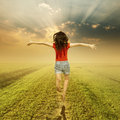 Happy woman jump on way of green grass and sunset Royalty Free Stock Photo