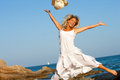 Happy woman jumping on beach. Royalty Free Stock Photography