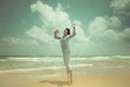 Happy woman jumping at the beach against blue sky background summer vacations concept Stock Photography