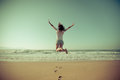 Happy woman jumping at the beach summer vacation concept freedom Stock Photo