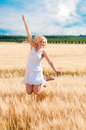 Happy woman jumping in golden wheat Royalty Free Stock Photo