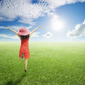 Happy Woman jumping in green grass fields with clouds sky Royalty Free Stock Photo