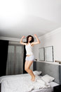 Happy woman jumping on her bed.