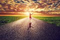 Happy woman jumping on long straight road, way towards sunset sun