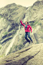 Happy woman jumping on rock in mountains Royalty Free Stock Photo