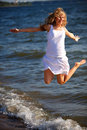 Happy woman jumping on the sea beach Stock Photos