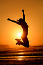 Happy woman jumping and sun successful dancing having fun on sunset in beach freedom happiness concept girl celebrating work out Stock Photos