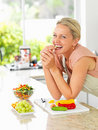 Happy woman in the kitchen making a salad Stock Photos