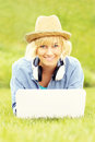 Happy woman with laptop on grass Royalty Free Stock Photo