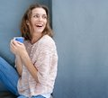 Happy woman laughing with a cup of coffee in hand Royalty Free Stock Photo