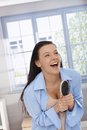 Happy woman laughing with hairbrush in hand Stock Photography