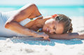 Happy woman laying on beach and playing with sand young in swimsuit Stock Photography