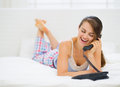 Happy woman laying in bed and talking phone Stock Photo