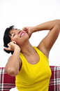 Happy woman listens to music beautiful wearing yellow top with wireless headphone Stock Images