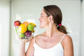 Happy woman looking at fruit bowl Royalty Free Stock Photo