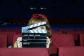 Happy woman looks through clap board beautiful in auditorium of movie theater Royalty Free Stock Photo