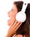Happy woman loving music headphones and singing isolated over white Royalty Free Stock Images