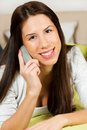 Happy woman lying on bed smiling, talking on her cellphone Royalty Free Stock Photo