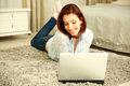 Happy woman lying on the floor and using laptop at home Royalty Free Stock Images