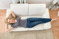 Happy Woman Lying On Sofa Royalty Free Stock Photo