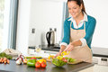 Happy woman making salad kitchen vegetables cooking