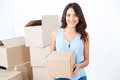 Happy woman moving in carrying carton boxes