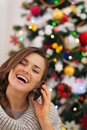 Happy woman near Christmas tree making phone call Stock Photos