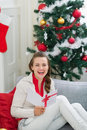 Happy woman near Christmas tree reading postcard Royalty Free Stock Photos